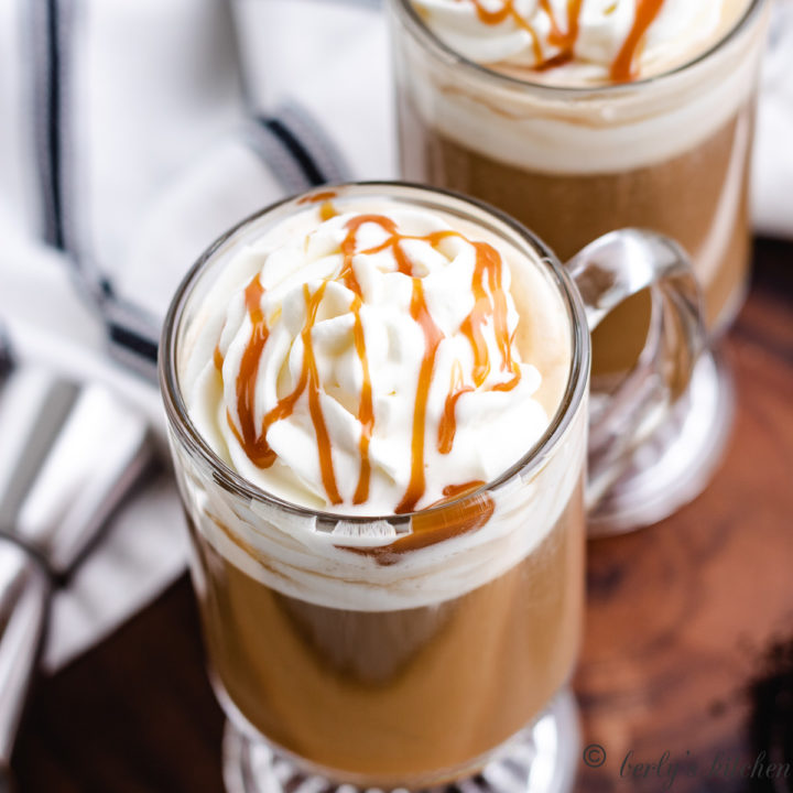 Top down view of whipped cream with caramel sauce on top of coffee.