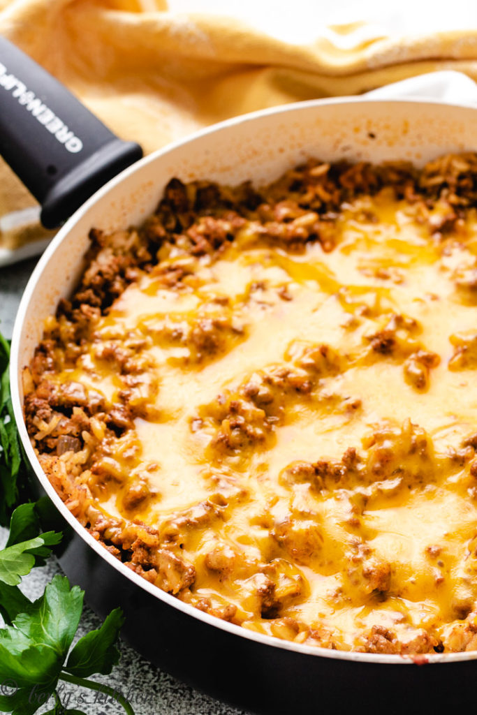 Cheesy rice and ground beef in a black pan.