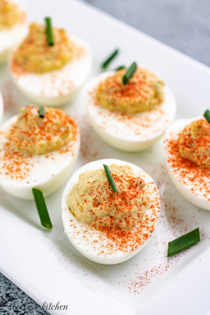 Several deviled eggs topped with diced green onions.
