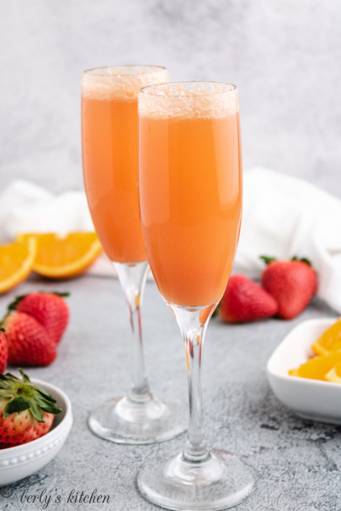 Two champagne glasses filled with strawberry mimosas.