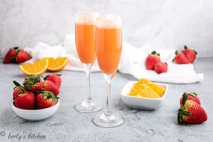 Mimosas in glasses with strawberries and oranges.