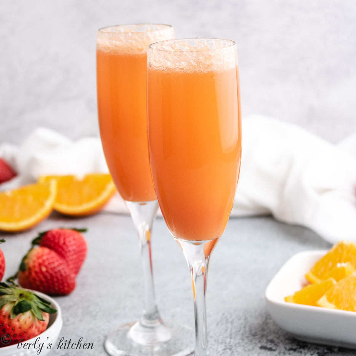 Two long stemmed glasses filled with strawberry mimosas.