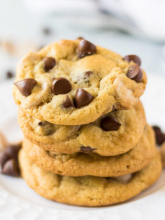 Four caramel chocolate chip cookies on a plate.