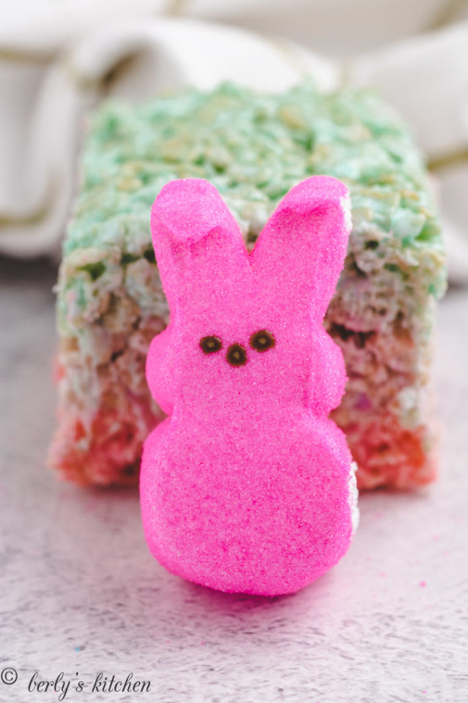 Pink peep in front of a rice krispie treat.