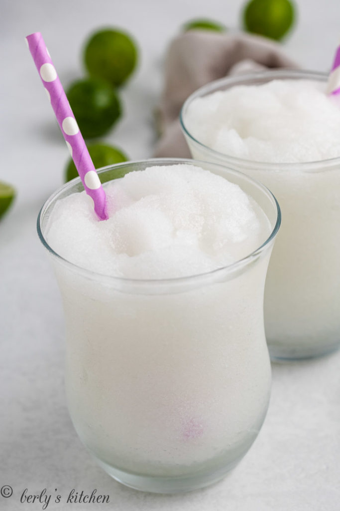 White frozen drink in a glass with a pink straw.