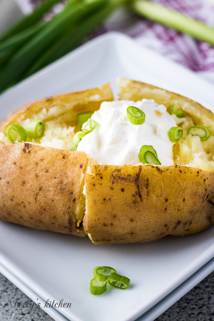 Instant pot baked potatoes on a plate with sour cream and chives.
