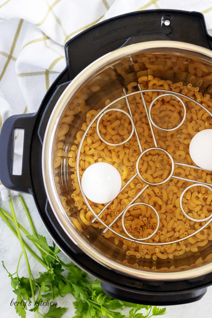 Dry macaroni, a trivet and two eggs, sitting in the pressure cooker.
