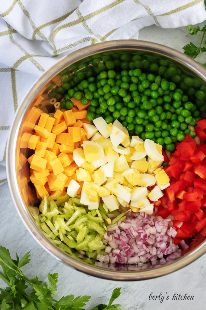 The vegetables have been added to the pressure cooker for mixing.