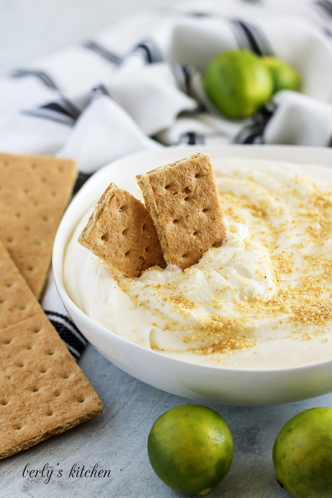 Key lime cheesecake dip, in a bowl, topped with graham cracker crumbs.