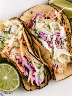 Top down view of fish tacos on a plate with fresh lime halves.