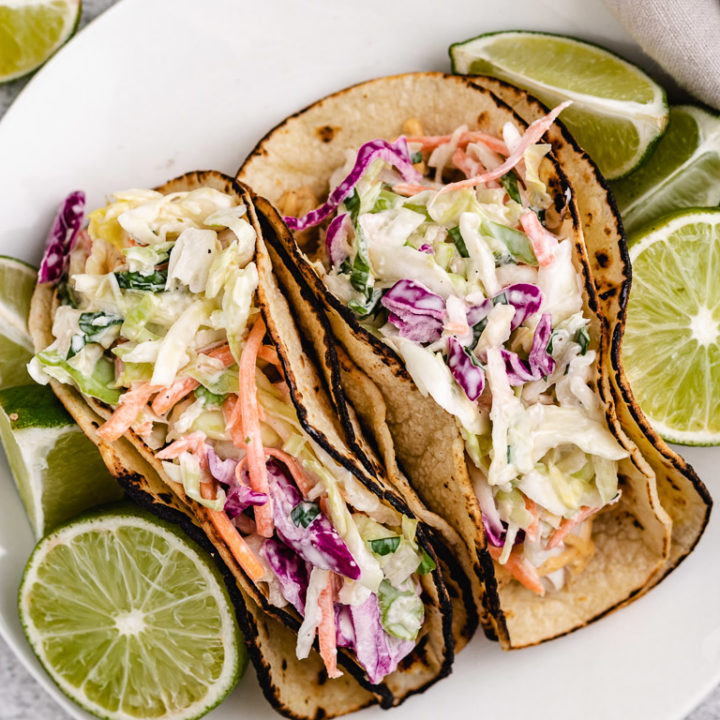 Top down view of mahi mahi tacos on a white plate.