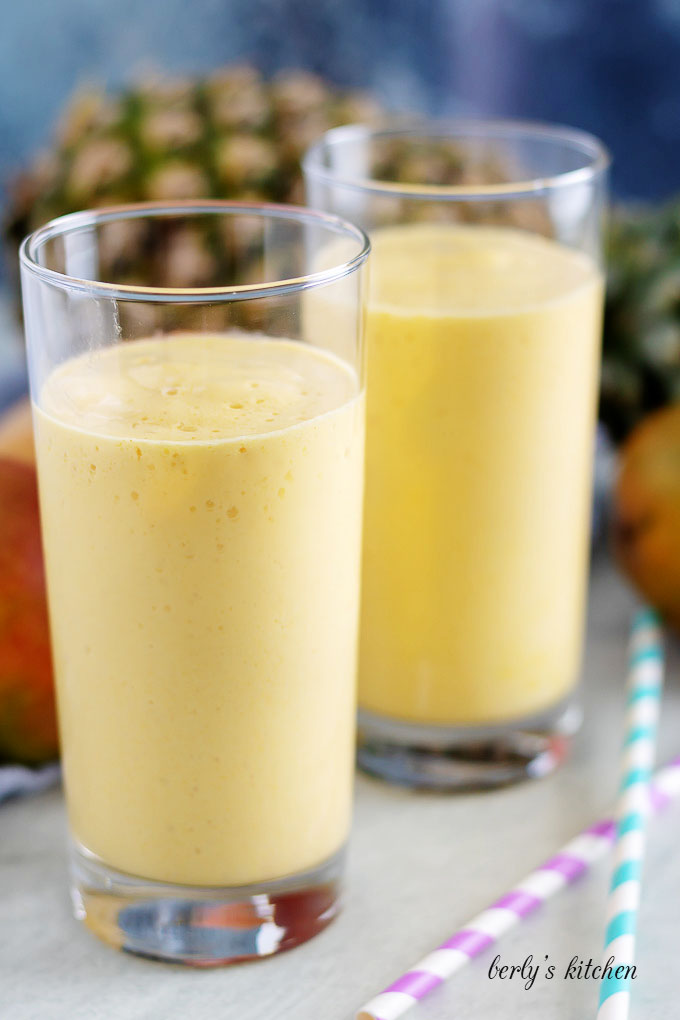 Two tall glasses filled with pineapple smoothie.