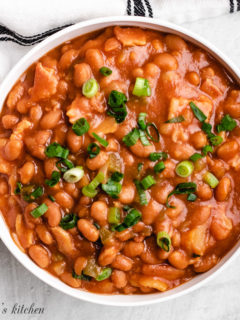 Close up of baked beans in a white dish.