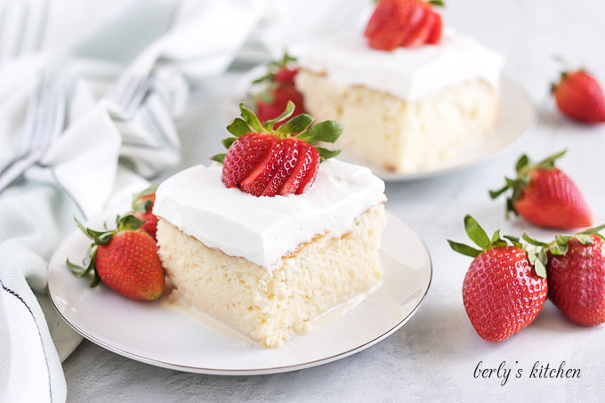 A piece of tres leches cake garnished with a sliced strawberry.