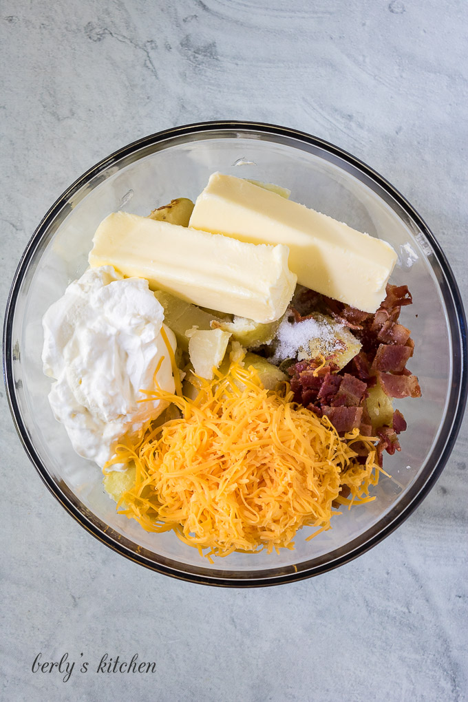 Butter, cheese, and other ingredients in a bowl for mashing.