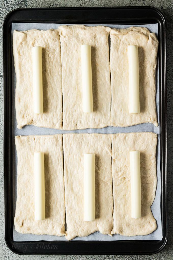 Mozzarella sticks on cut pizza dough.