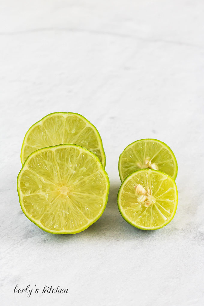 Key limes cut in half and stacked next to each other.