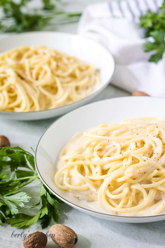 Two bowls of pasta tossed in white sauce.