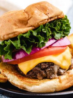 Stuffed burger on a black plate.