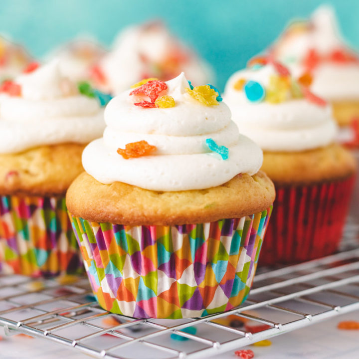 Several cupcakes topped with colorful cereal.