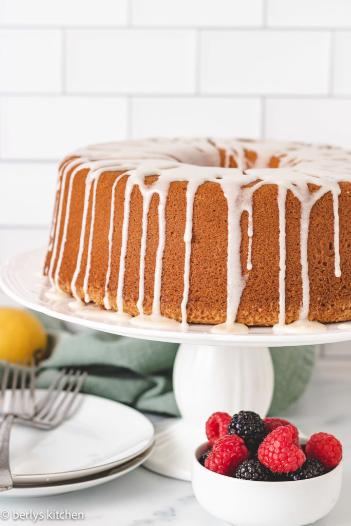 Pound cake drizzled with icing on a cake stand.