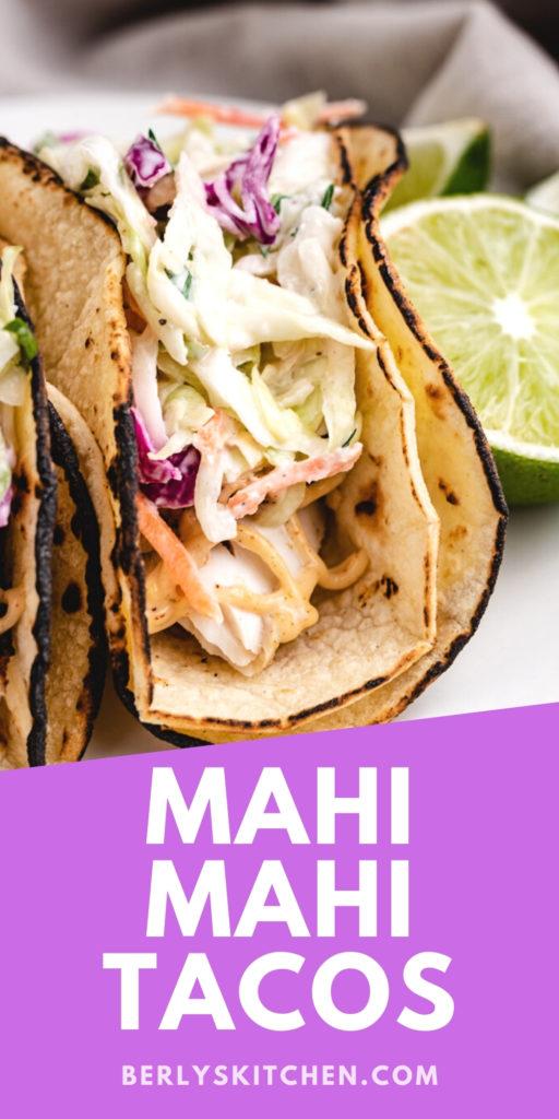 Two mahi mahi tacos on a plate.