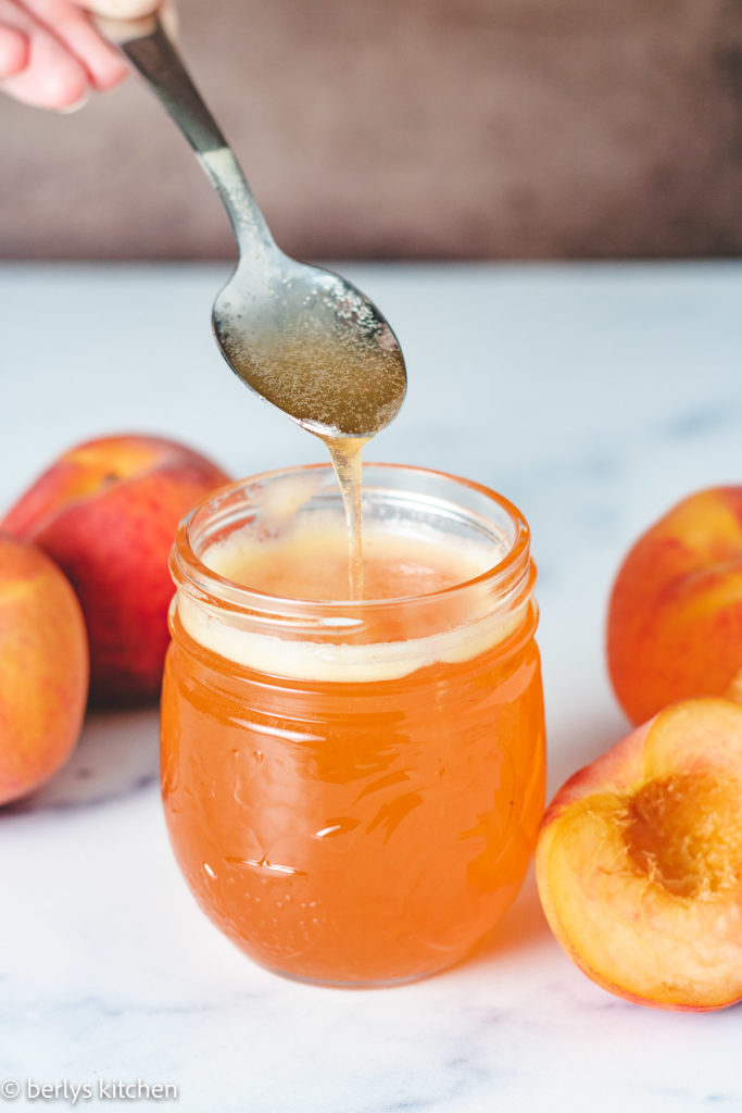 Fresh peach syrup on a spoon.