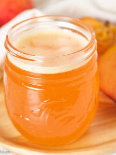 Peach syrup in a jar next to fresh peaches.