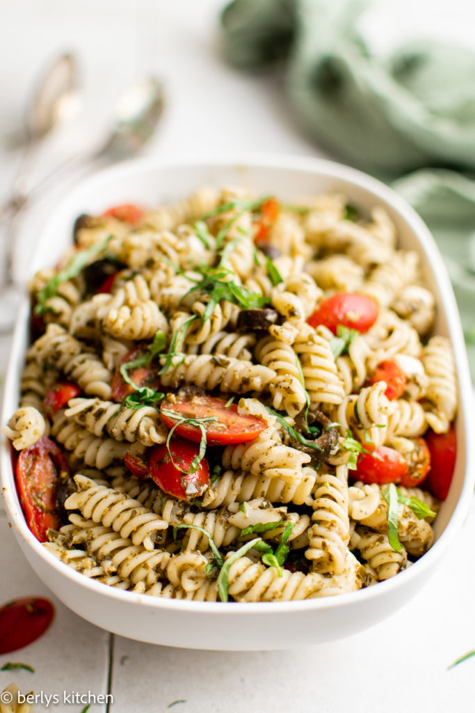 Serving dish filled with basil pesto pasta salad.