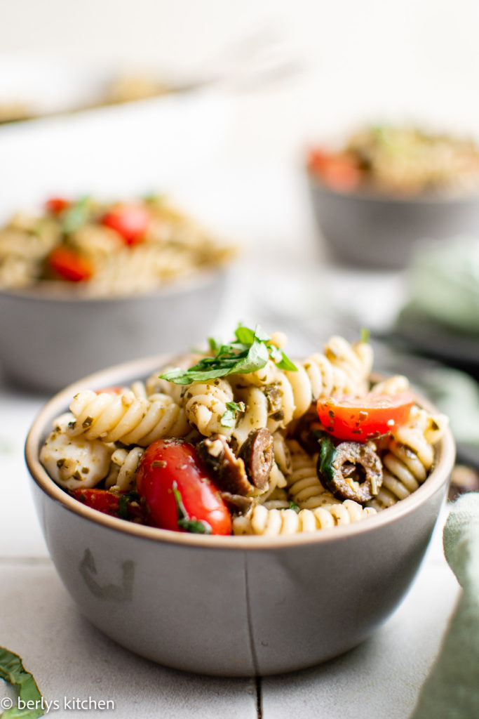 Gray bowl filled with pasta salad with olives and tomatoes.