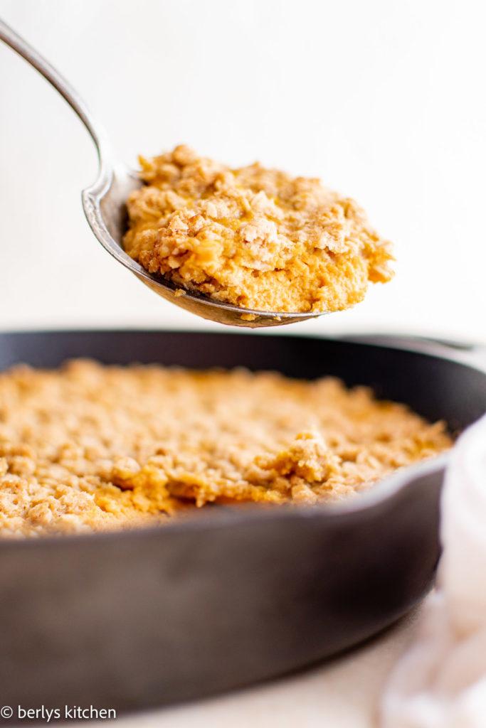 Spoon scooping pumpkin crisp out of a pan.
