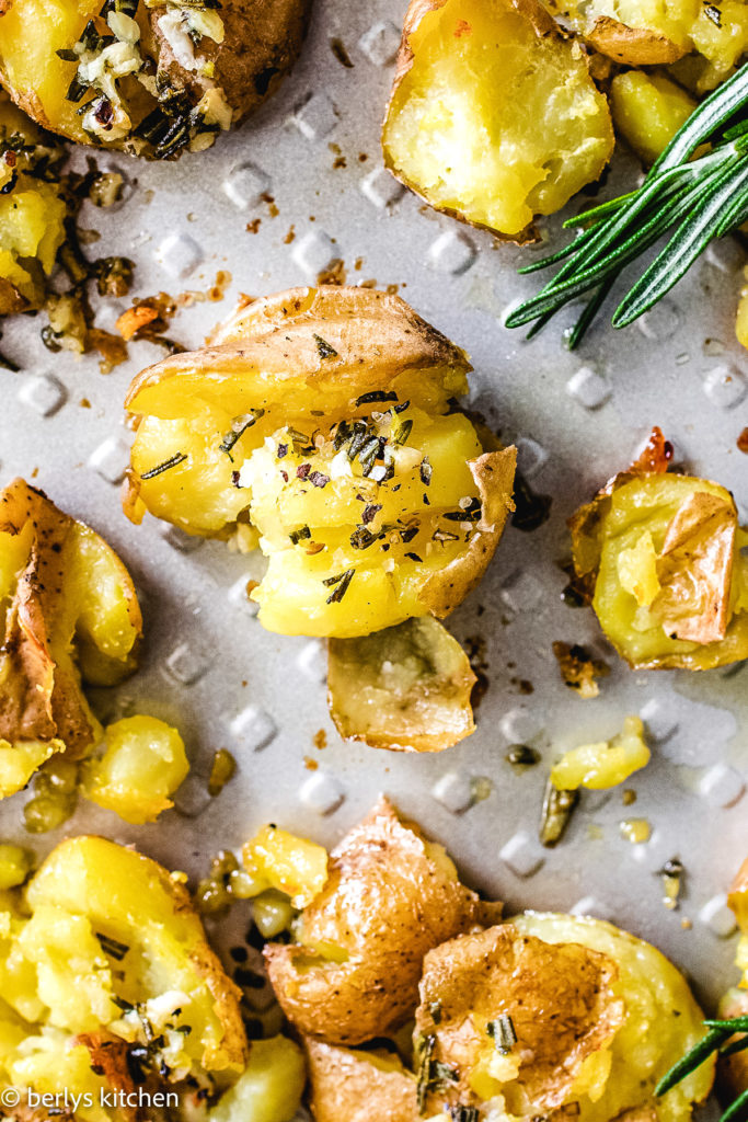 Top down view of smashed potatoes with herb butter.