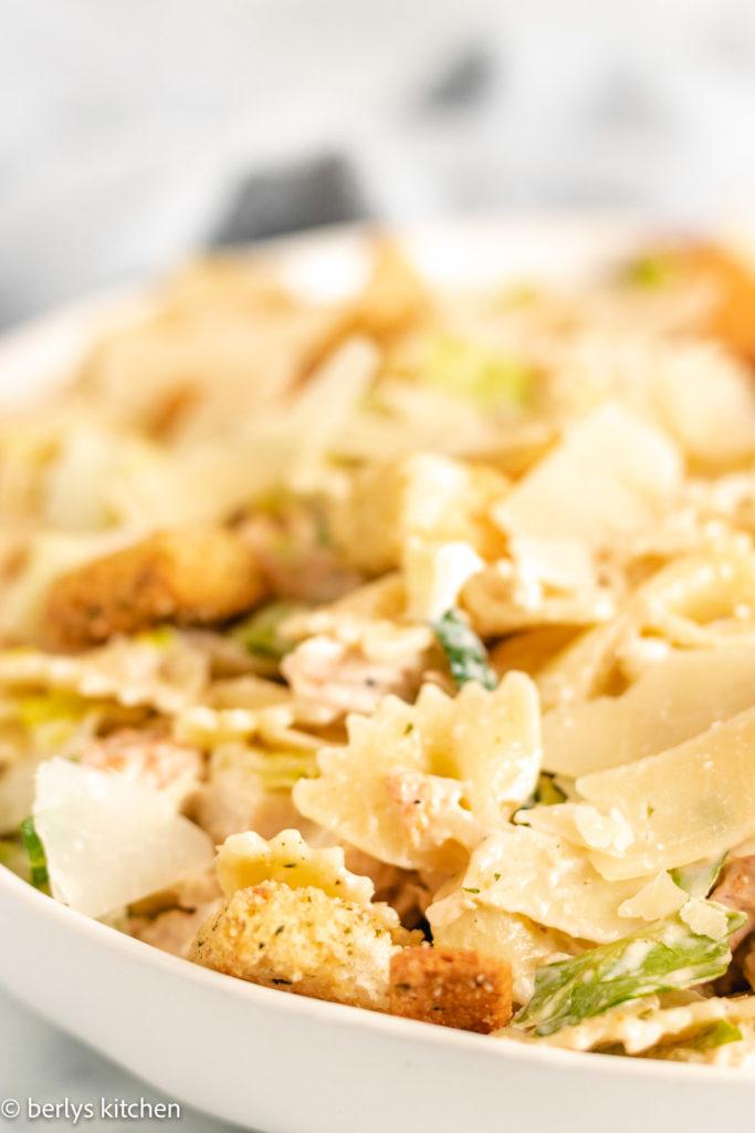 Bowtie chicken caesar pasta salad in a white bowl.