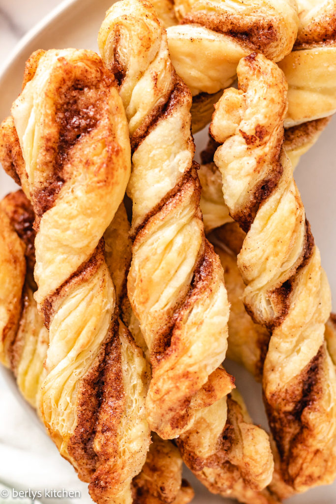 Top down view of several cinnamon twists on a plate.