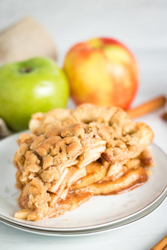 Slice of dutch apple pie on a white plate.