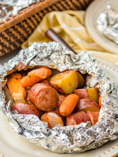 Serving of sausage and potatoes foil packet on a tan plate.