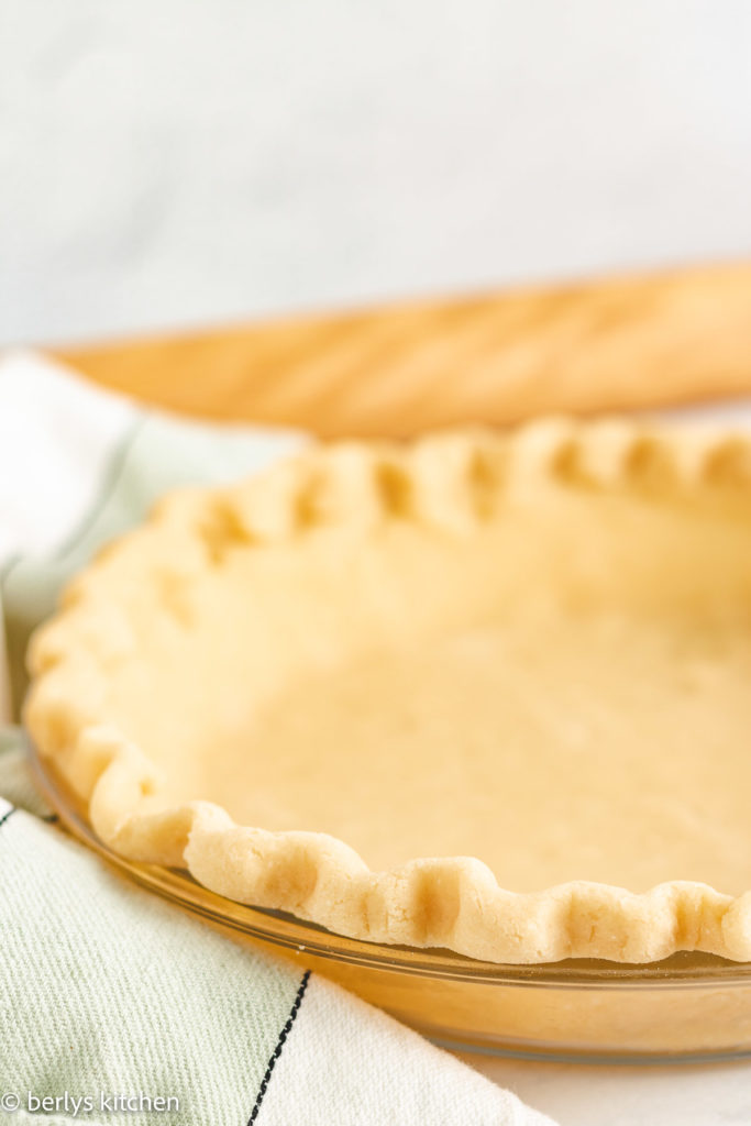 Pie crust with butter in a glass pie dish.