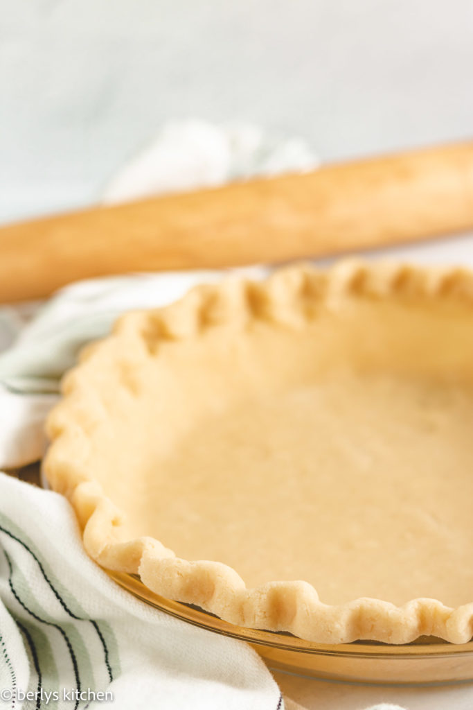 Pie crust with butter next to a rolling pin.