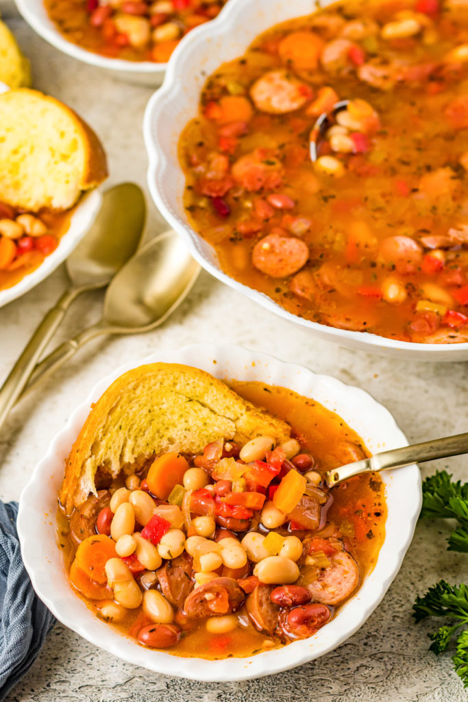 Top down view of sausage and bean soup with bread.