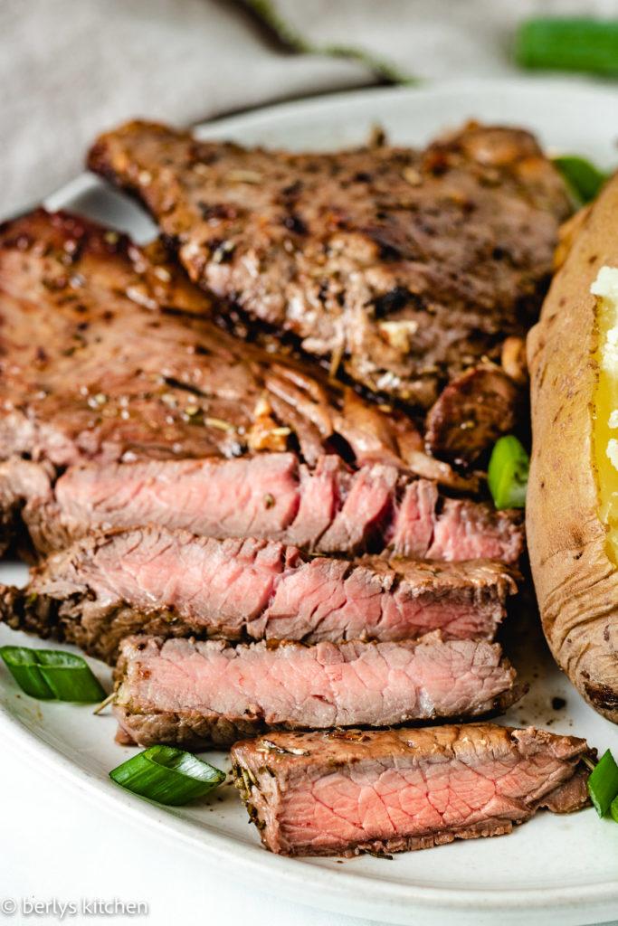 Close up of slicedsirloin steak on a plate.