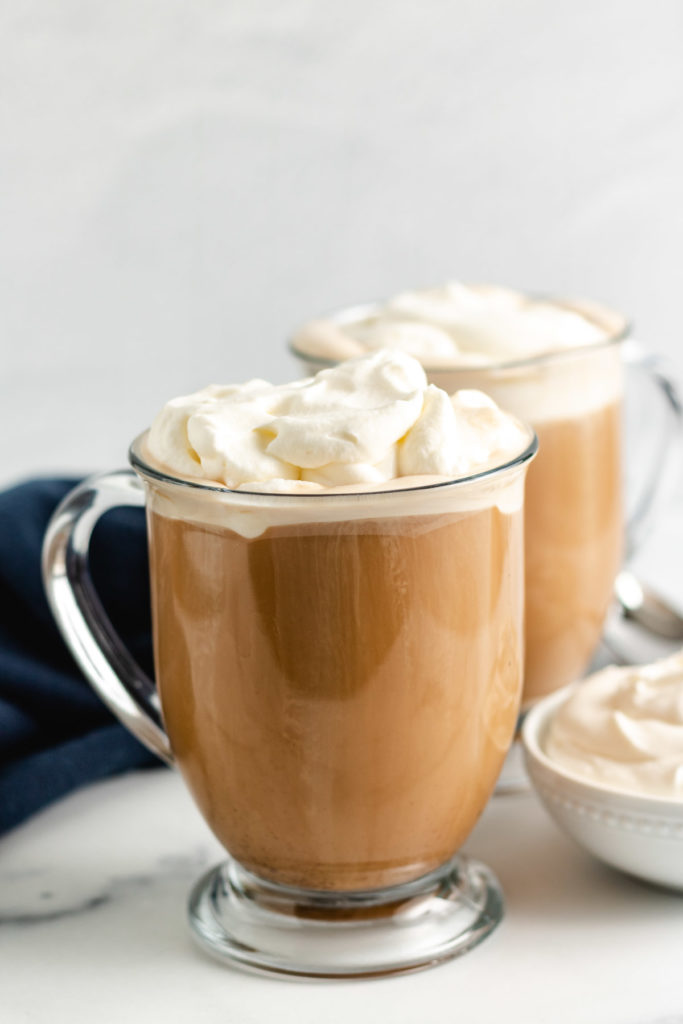 Two mugs of boozy coffee with whipped cream.