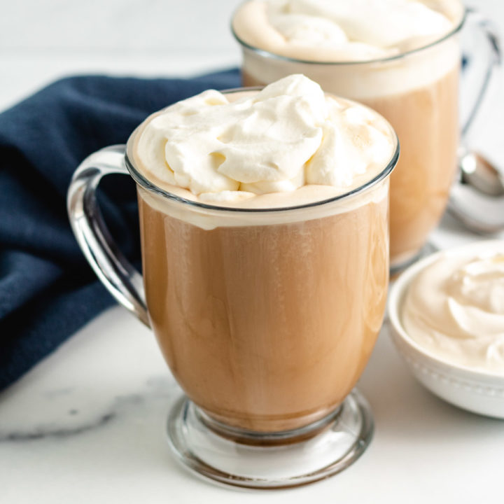 Two coffee mugs filled with amaretto coffee and whipped cream.
