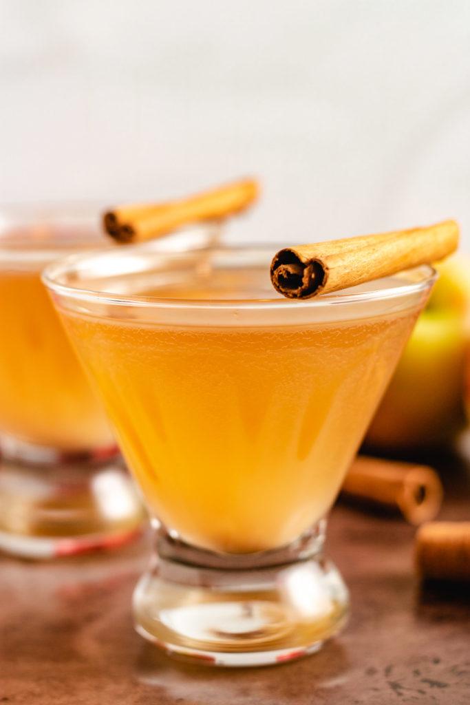 Two martinis with cinnamon sticks.