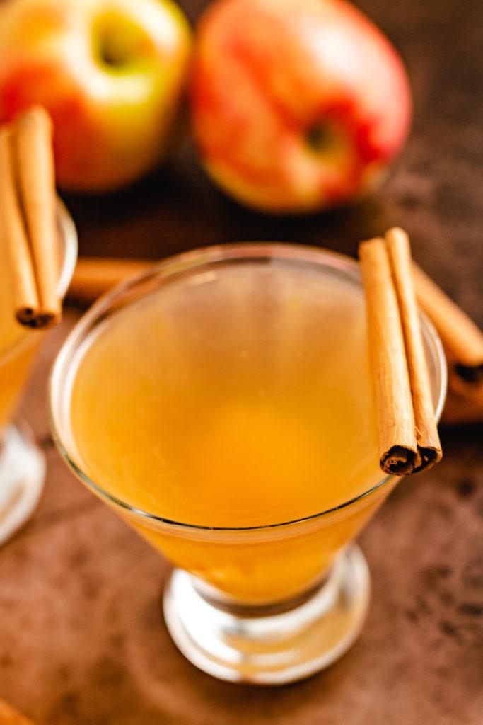 Apple cider martini with cinnamon sticks.