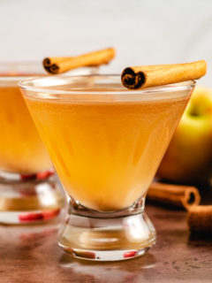 Two apple martinis with fresh apples.