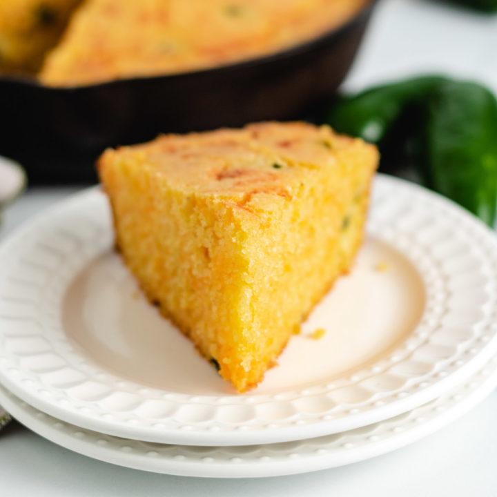 Slice of cornbread on 2 white plates.