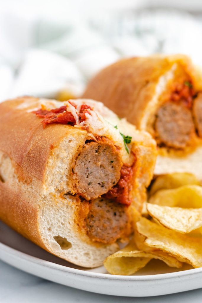 Two half meatball sub sandwiches with potato chips.