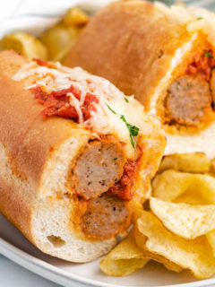 Meatball sandwich cut in half on a gray plate with chips.