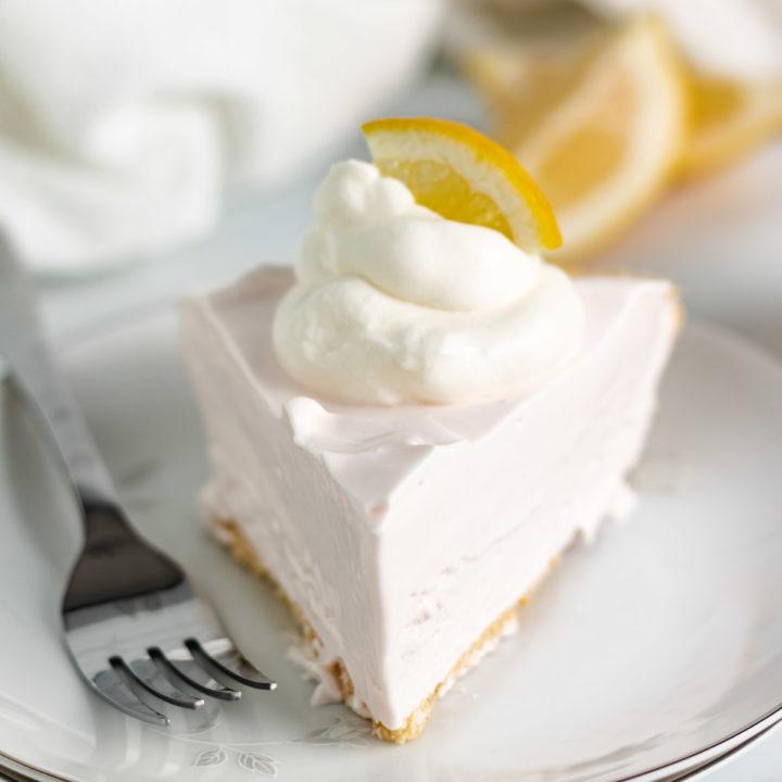 Slice of lemonade pie on a white dish.