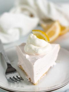 Slice of frozen lemonade pie with lemon wedges.
